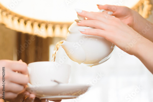 Tea party. Women pour green tea into a white Cup © YouraSasin