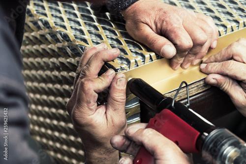 Leinwandbild Motiv Workers assembling metal frames with rivet gun on the production line