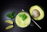 Avocado smoothie with lime and mint on black background. Top view with selective focus.
