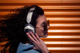 Beautiful young girl with dark curly hair listening to music on headphones, street style, outdoor portrait, hipster girl, music, mp3, Bali, beauty woman, sunglasses, orange color, concept dj