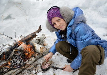 woman preparing food in the winter forest at the stake