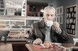 Kind mature man drinking tasty coffee during pause