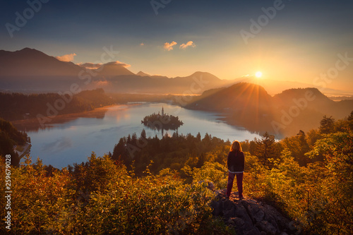 Leinwandbild Motiv Girl looking scenery of Bled lake in Slovenia