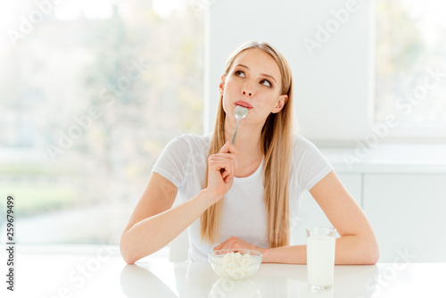 Leinwandbild Motiv Portrait of charming cute teen student dream dreamy  teenager have  delicious yogurt  dish feel delight pleasure satisfied say yummy use silverware beautiful trendy outfit sit apartment