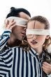 Blonde model with blindfold touching face of handsome colleague