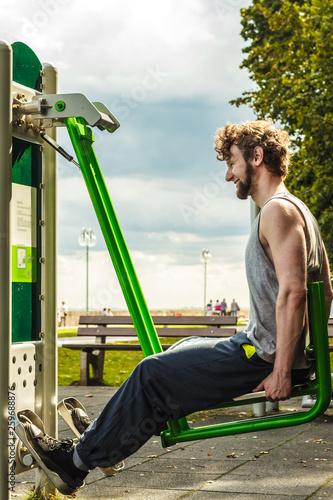 Fototapeten Fitness Active man exercising on leg press outdoor.