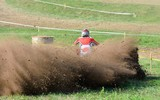 Back view of unrecognizable ATV rider in motion.