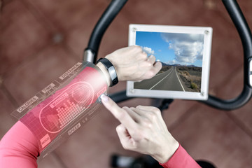 Techno concept: a girl on a stationary bike is watching an electronic screen fitness bracelet
