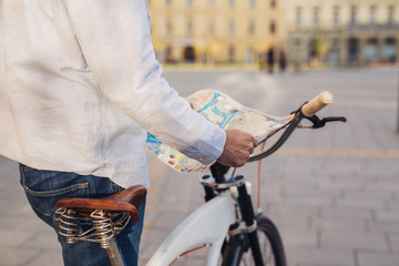 exploring the city with bicycle. man standing beside bicycle and holding street town map
