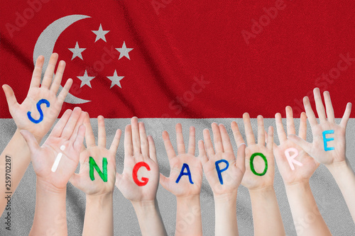 Singapore inscription on the children's hands against the background of a waving flag of the Singapore
