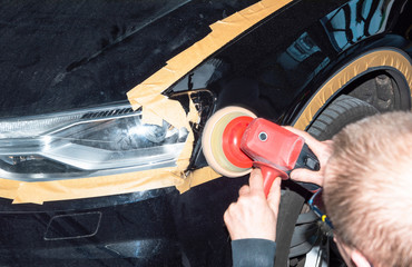 Professioneller Autolackierer poliert ein Fahrzeugteil mit der Poliermaschine - Serie Autowerkstatt
