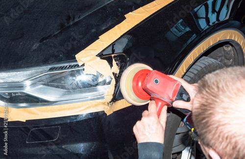 Leinwandbild Motiv Professioneller Autolackierer poliert ein Fahrzeugteil mit der Poliermaschine - Serie Autowerkstatt