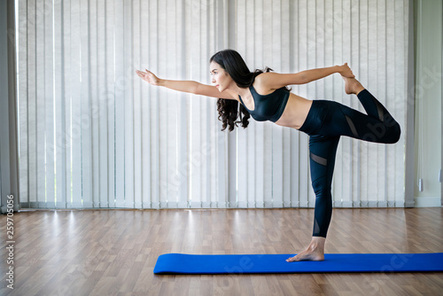 Leinwandbild Motiv Young woman practicing yoga position in an indoor gym studio. Healthy and wellness lifestyle concept.