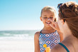 Mother applying suntan lotion on daughter face