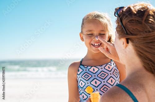 Leinwandbild Motiv Mother applying suntan lotion on daughter face