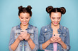 Leinwandbild Motiv Portrait of cute attractive funny cheerful hipsters looking holding devices using modern technology applications searching information dressed in denim clothes isolated on azure background