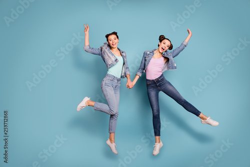 Leinwandbild Motiv Fooling. Full length body size view photo of cute ladies isolated excited rejoice enjoy make v-sign hold hands have perfect weekends holidays dressed in denim clothing pastel background