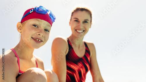 Leinwanddruck Bild Smiling girl with swimming trainer