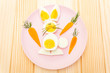 Leinwanddruck Bild - Easter bunny (rabbit) eggs children (kids) food concept. With carrot on rosy (pink) plate. Wooden background, top view