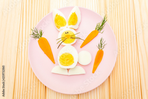 Leinwanddruck Bild Easter bunny (rabbit) eggs children (kids) food concept. With carrot on rosy (pink) plate. Wooden background, top view