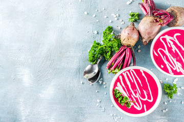 Spring vegetable soup. Homemade beet cream soup, with fresh organic beetroot, sour cream and herbs, blue concrete background copy space