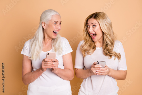 Leinwandbild Motiv Portrait of nice-looking lovely attractive charming cute cheerful cheery positive crazy glad ladies wearing white t-shirt using wireless connection speed isolated over beige pastel background