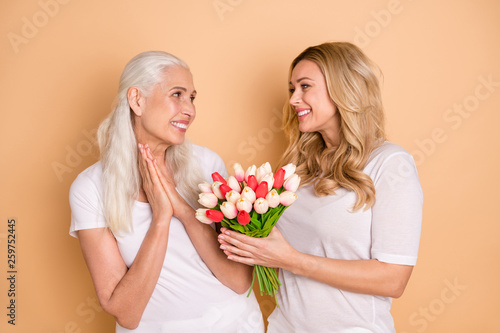 Leinwandbild Motiv Portrait of charming beautiful curly grey haircut person receive blooming greeting 8-march anniversary feel glad enjoy leisure lifestyle wear trendy t-shirts isolated on pastel background