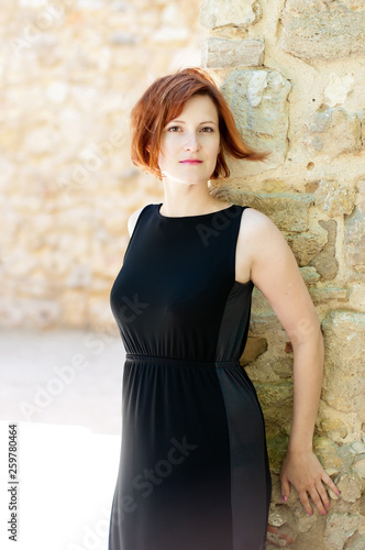 Woman in black dress on stone wall background - 259780464