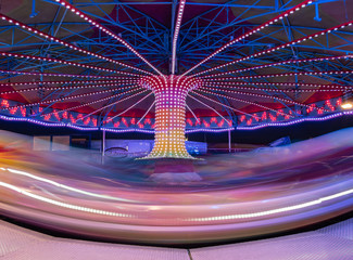 view of a giant ferris wheel attraction in long exposure full of colors at night
