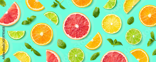 Colorful pattern of citrus fruit slices and mint leaves - 259793658