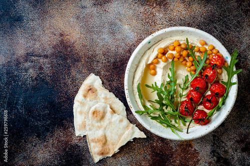 Homemade hummus with roasted cherry tomatoes. Middle Eastern traditional and authentic arab cuisine. Top view, copy space - 259798618