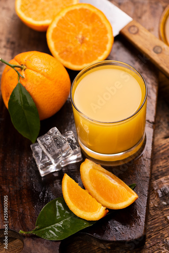 Leinwanddruck Bild Glass of orange juice on wooden table