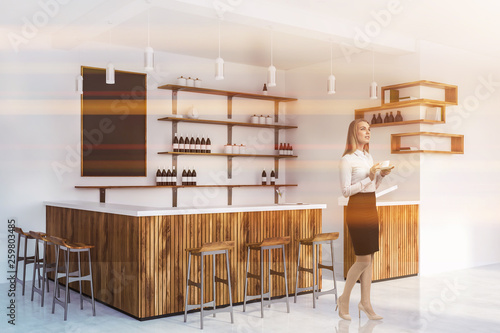 Leinwanddruck Bild Blonde woman in wooden bar interior