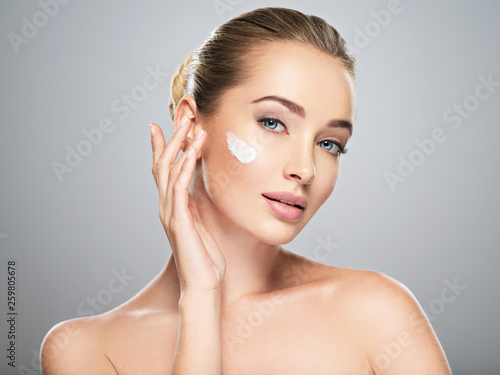 canvas print picture woman gets cream in the face. Skin care concept.