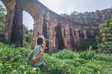 Woman looks at the Demodara nine arches bridge the most visited sight of Ella town in Sri Lanka