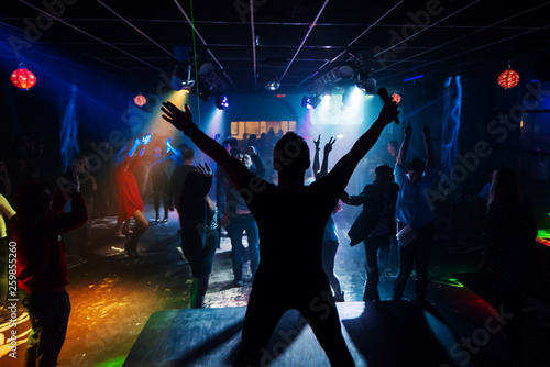 silhouette of the singer at a live concert at the club at the event against the crowd - 259855260