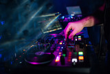 hands DJ playing and mixing music on music controller at a party