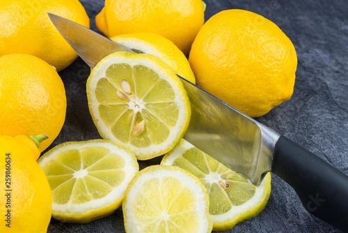 canvas print picture Ein scharfes Küchemesser schneidet eine Zitrone in Scheiben