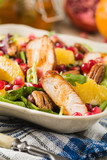 Spring salad with chicken, pomegranate, orange, pecan nuts and honey.