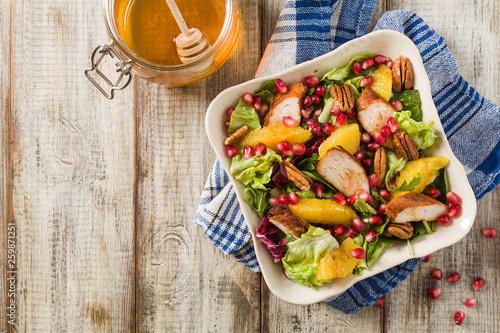 fototapeta na ścianę Spring salad with chicken, pomegranate, orange, pecan nuts and honey.