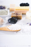 spa massage mud and clay powder, soaps, bath salt, shea butter and lavenders on white wood table background