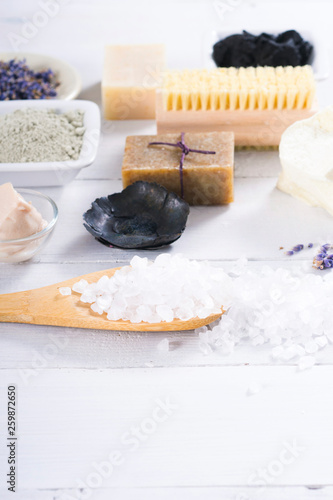 spa massage mud and clay powder, soaps, bath salt, shea butter and lavenders on white wood table background - 259872650