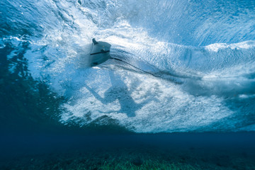 Underwater view of the surfer riding the crystal clear ocean wave and making sharp turn