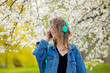 girl in a denim jacket and headphones stands near a flowering tree