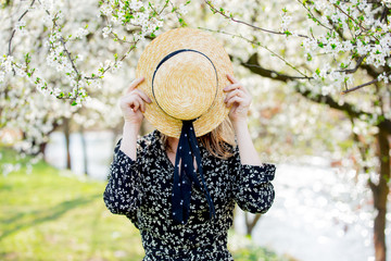 Young girl in a hat stay near a flowering tree