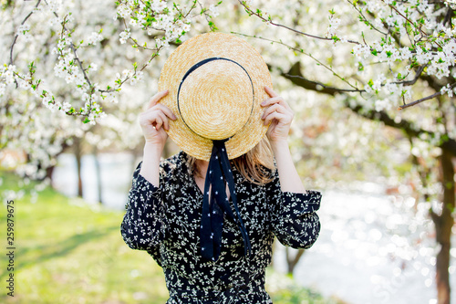 Young girl in a hat stay near a flowering tree © Masson