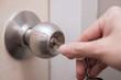 Leinwandbild Motiv Close up of woman's hand using key for unlocking or locking the white door