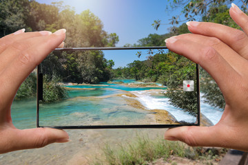 Taking photo by mobile phone waterfall on the river.