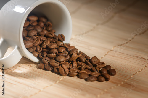 coffee beans are poured from a white Cup © Владимир Зубков