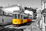 Yellow and red vintage trams on old streets of Lisbon, Alfama, Portugal, popular touristic attraction and destination. Black and white picture with a coloured tram.